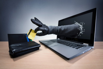 Stealing a credit card through a laptop concept for computer hacker, network security and electronic banking security