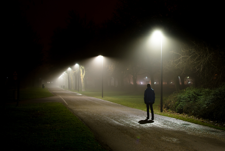 Single Person Walking on Street in the Dark Night